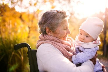 Elderly lady holding baby in Autumn